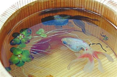 用木盆盛载的立体金鱼作品